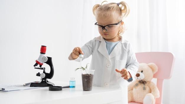 Vorderansicht des niedlichen kleinkindes, das über wissenschaft mit pflanze und mikroskop lernt Kostenlose Fotos