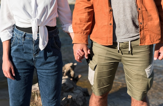 Vorderansicht des romantischen paares, das hände hält, während am strand Kostenlose Fotos