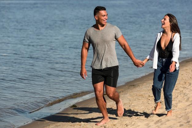 Vorderansicht des romantischen paares, das hände hält, während man am strand spazieren geht Kostenlose Fotos