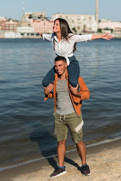 Vorderansicht des romantischen paares, das zeit am strand verbringt Kostenlose Fotos