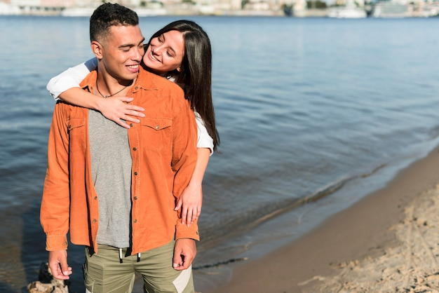 Vorderansicht des romantischen paares, das zusammen am strand aufwirft Kostenlose Fotos