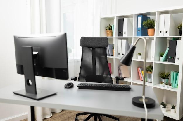 Vorderansicht des schreibtischs mit computer und stuhl Kostenlose Fotos