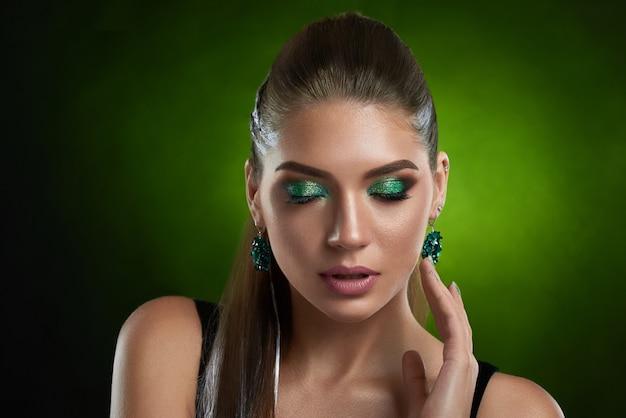 Vorderansicht des sinnlichen brünetten mädchens mit glänzendem grünem make-up, das perfekte bronzehaut des gesichts berührt. schöne frau mit geschlossenen augen, im schwarzen oberteil tragend, großes rundes ohrring verführerisches aufstellen. Premium Fotos