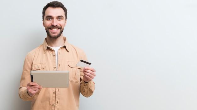 Vorderansicht des smiley-mannes, der online mit kreditkarte einkauft Kostenlose Fotos