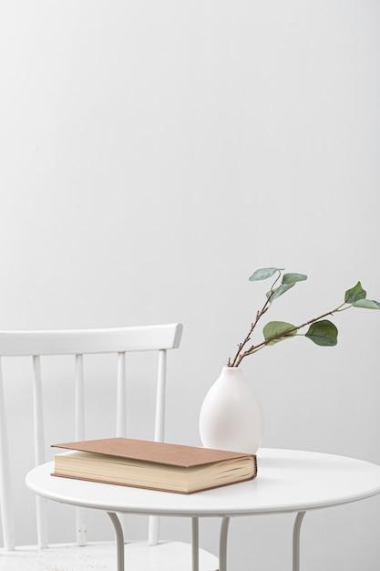 Vorderansicht des tisches mit buch und vase Kostenlose Fotos