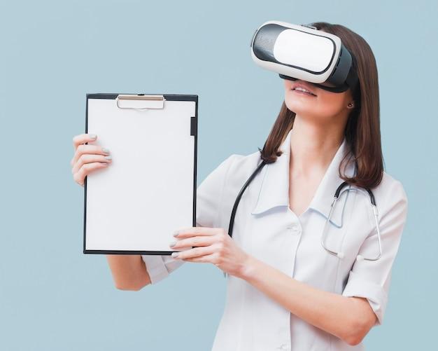 Vorderansicht des weiblichen arztes, der notizblock hält, während das virtual-reality-headset trägt Kostenlose Fotos