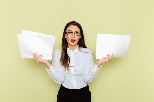 Vorderansicht des weiblichen büroangestellten im weißen hemd und im schwarzen rock, die papiere auf hellgrüner wand halten Kostenlose Fotos