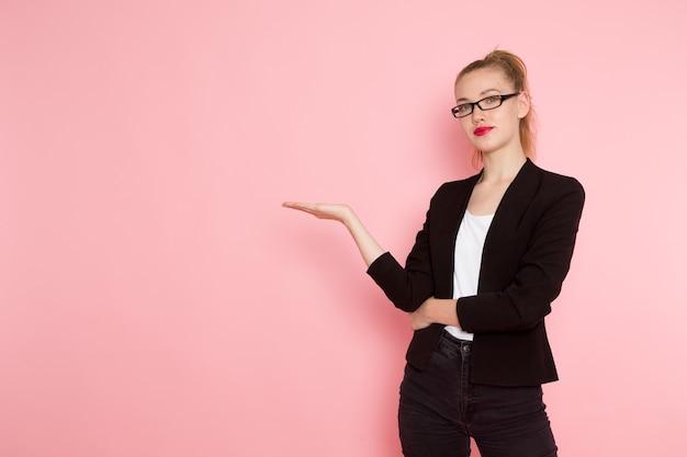 Vorderansicht des weiblichen büroangestellten in der schwarzen strengen jacke, die gerade auf der rosa wand aufwirft Kostenlose Fotos