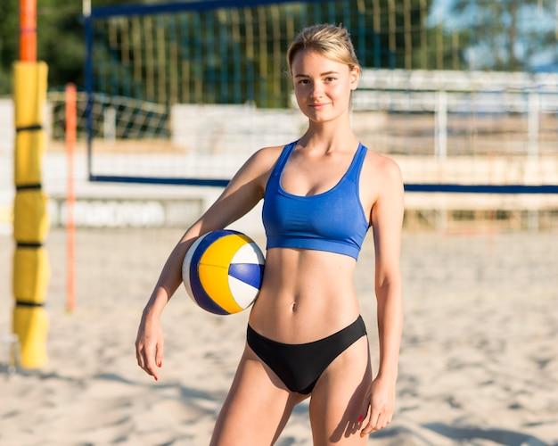 Vorderansicht des weiblichen volleyballspielers, der ball am strand beim aufstellen hält Kostenlose Fotos