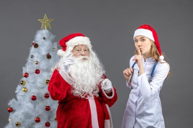 Vorderansicht des weihnachtsmannes mit der jungen ärztin an der grauen wand Kostenlose Fotos