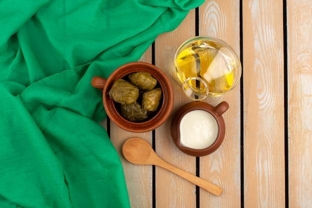 Vorderansicht dolma berühmte östliche mahlzeit mit hackfleisch im inneren zusammen mit joghurt und olivenöl auf dem braunen boden Kostenlose Fotos