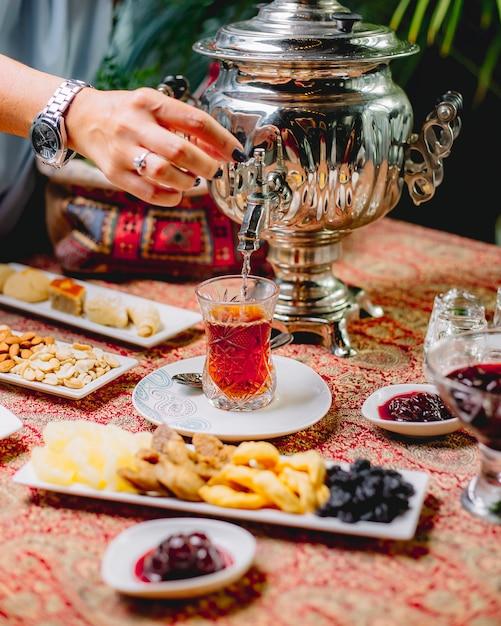 Vorderansicht eine frau gießt tee aus einer samowar-teekanne in ein glas armuda auf einer untertasse Kostenlose Fotos