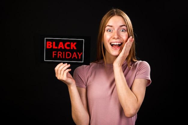 Vorderansicht einer begeisterten frau, die eine schwarze freitag-karte hält Kostenlose Fotos
