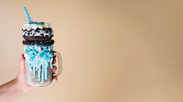 Vorderansicht einer hand, die ein milchshake mit normalem hintergrund hält Kostenlose Fotos