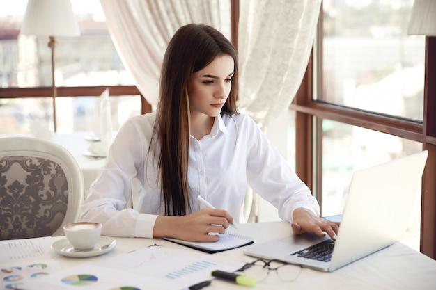 Vorderansicht einer jungen brunettegeschäftsfrau, die an dem laptop arbeitet und etwas notiert Kostenlose Fotos