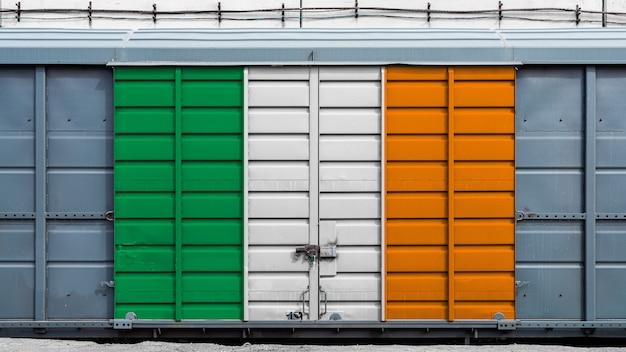 Vorderansicht eines containerzuggüterwagens mit einem großen metallverschluß mit der staatsflagge von irland. das konzept des exports und imports, des transports, der nationalen lieferung von waren Premium Fotos