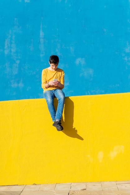 Vorderansicht eines jungen, der die zufällige kleidung sitzt auf einem gelben zaun gegen eine blaue wand bei der anwendung eines smartphone trägt Premium Fotos