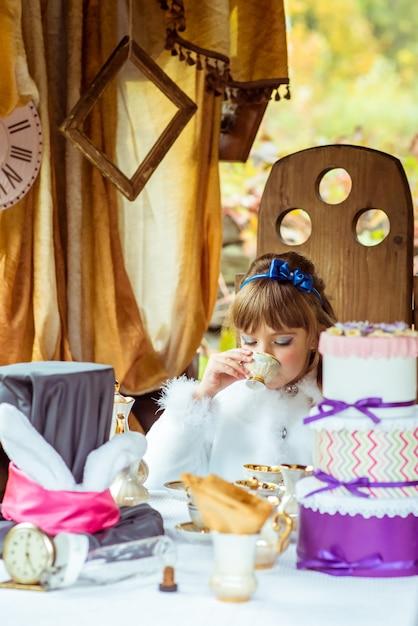 Vorderansicht eines kleinen schönen mädchens in der landschaft einen tee am tisch im park trinkend Premium Fotos