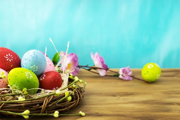 Vorderansicht eines ostereies im nest mit frühlingsblumenzweigen auf braunem holz und türkishintergrund. Premium Fotos