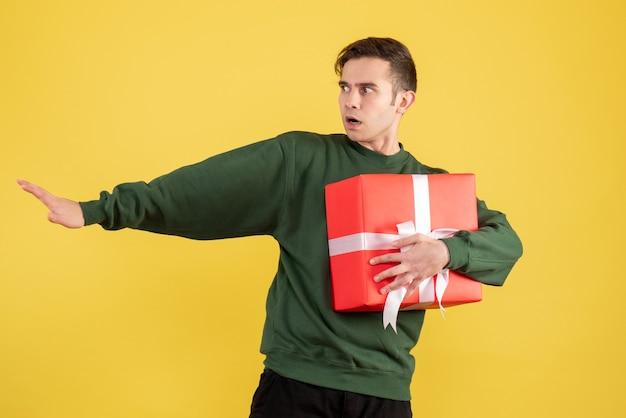 Vorderansicht erschreckter mann mit grünem pullover, der geschenk auf gelb hält Kostenlose Fotos