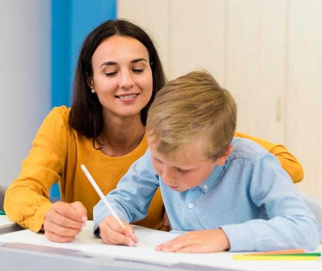 Vorderansicht frau hilft ihrem schüler in der klasse Kostenlose Fotos