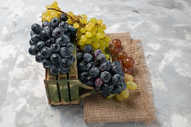 Vorderansicht frische trauben saftige und milde früchte auf weißem schreibtisch Kostenlose Fotos