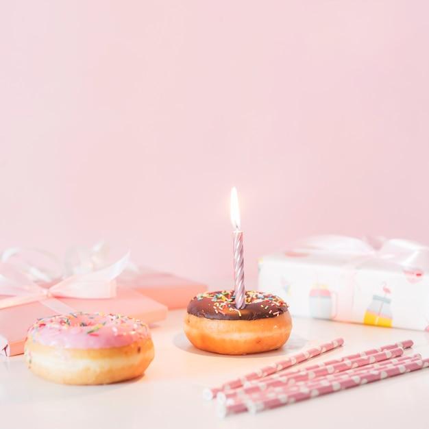 Vorderansicht geburtstag donut mit brennender kerze Kostenlose Fotos