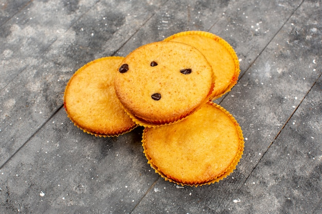Vorderansicht gelb gefärbte kuchen lecker auf dem grauen holz rustikal gekocht Kostenlose Fotos