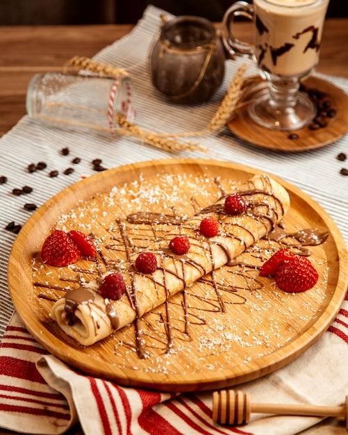 Vorderansicht gerollter pfannkuchen mit schokoladenglasur und erdbeeren Kostenlose Fotos