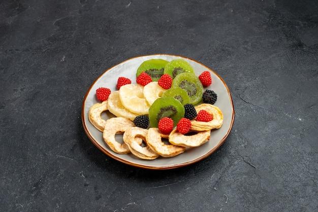 Vorderansicht getrocknete ananasringe mit getrockneten kiwis und äpfeln auf dunkelgrauer oberfläche frucht trockene rosine süße zuckersüßigkeit Kostenlose Fotos