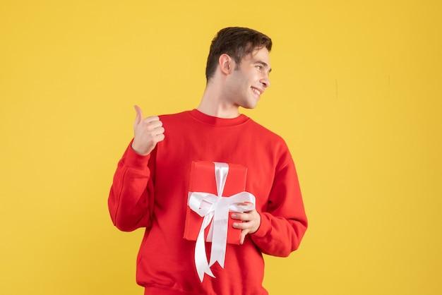 Vorderansicht glücklicher junger mann, der auf gelb steht Kostenlose Fotos
