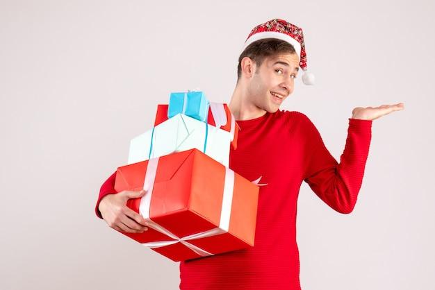 Vorderansicht glücklicher junger mann mit weihnachtsmütze, die auf weiß steht Kostenlose Fotos