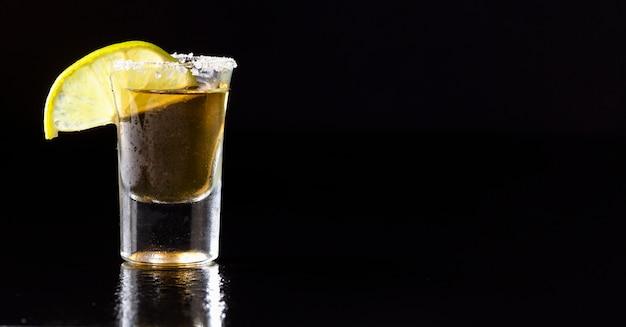 Vorderansicht gold tequila schuss mit kalk und kopierraum Kostenlose Fotos