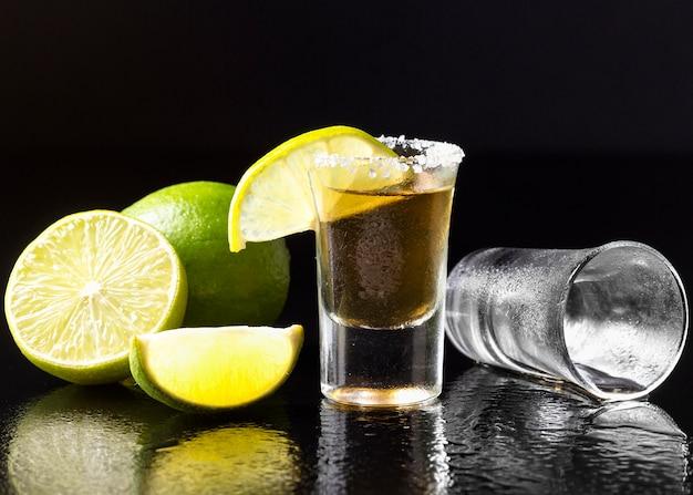 Vorderansicht gold tequila schuss mit limette und salz Kostenlose Fotos