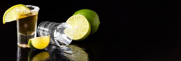 Vorderansicht gold tequila schuss und kalk mit kopierraum Kostenlose Fotos