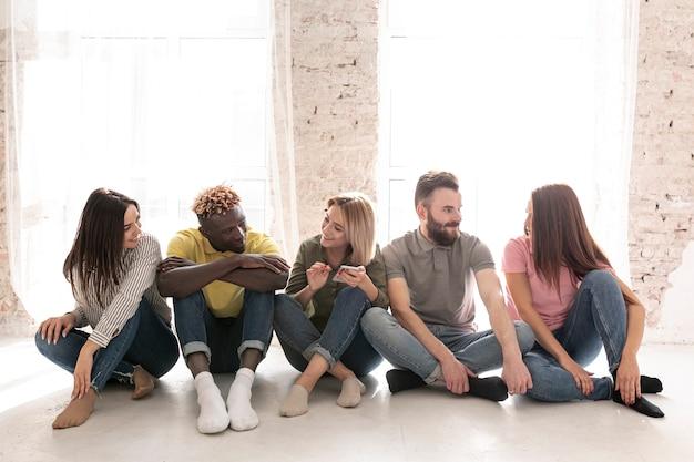 Vorderansicht gruppe von freunden auf dem boden Kostenlose Fotos