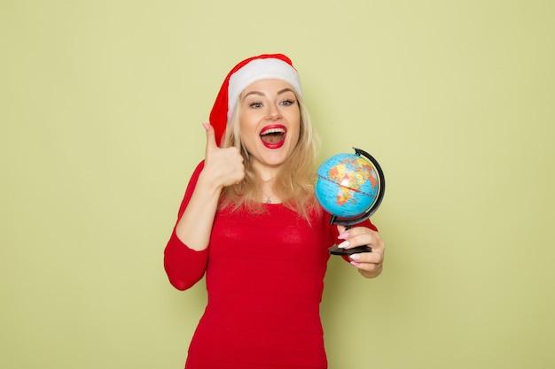 Vorderansicht hübsche frau, die kleine erdkugel auf grünen wandfeiertagsgefühle weihnachten neujahrsschneefarben hält Kostenlose Fotos