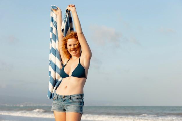 Vorderansicht hübsches junges mädchen, das am strand lächelt Kostenlose Fotos