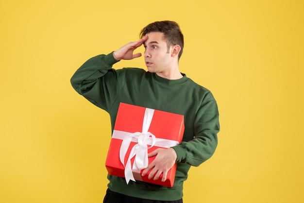Vorderansicht interessierter mann mit grünem pullover, der auf gelb steht Kostenlose Fotos