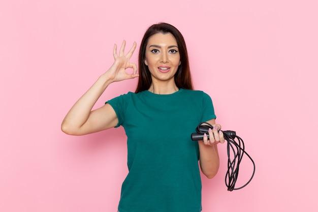 Vorderansicht junge frau im grünen t-shirt springseil auf hellrosa wand taille sport übung workouts schönheit schlanke sportlerin weiblich Kostenlose Fotos