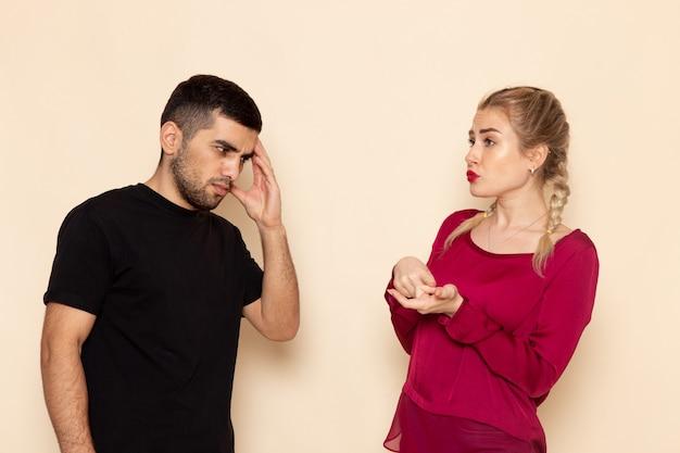 Vorderansicht junge frau im roten hemd, das mit dem jungen mann auf der konfrontation des weiblichen stoffes des cremeraums streitet Kostenlose Fotos
