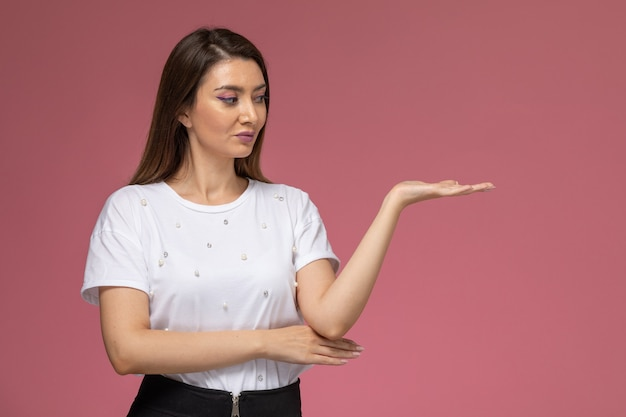 Vorderansicht junge frau im weißen hemd, das mit erhabener hand auf der rosa wand aufwirft, farbfrau stellt modellfrau dar Kostenlose Fotos