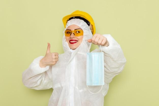Vorderansicht junge frau im weißen spezialanzug und im gelben helm, der sterile maske mit leichtem lächeln auf der grünraumchemie hält s Kostenlose Fotos