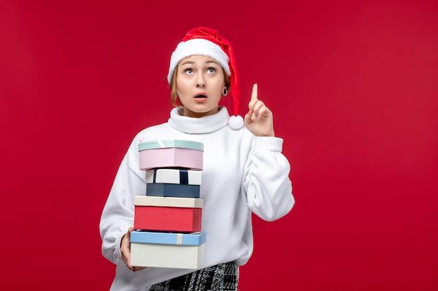 Vorderansicht junge frau mit neujahrsgeschenken auf rotem hintergrund Kostenlose Fotos