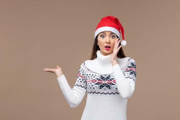 Vorderansicht junge frau mit weihnachtsumhang auf dem braunen hintergrundfeiertagsemotionsweihnachten Kostenlose Fotos