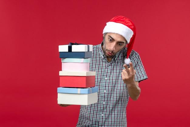 Vorderansicht junger mann, der anzahl der geschenke auf rotem hintergrund zählt Kostenlose Fotos