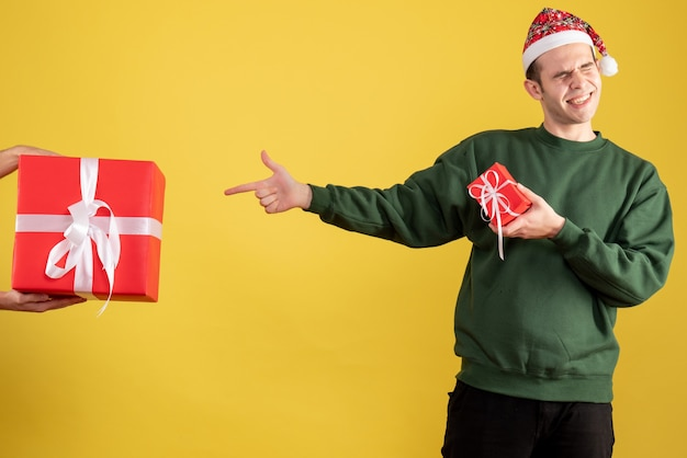 Vorderansicht junger mann, der auf das geschenk in der weiblichen hand auf gelb zeigt Kostenlose Fotos