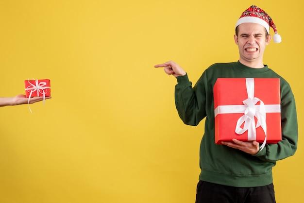 Vorderansicht junger mann, der augen schließt, die auf geschenk in weiblicher hand auf gelb zeigen Kostenlose Fotos