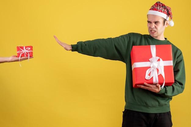 Vorderansicht junger mann, der das geschenk in der weiblichen hand auf gelb ablehnt Kostenlose Fotos