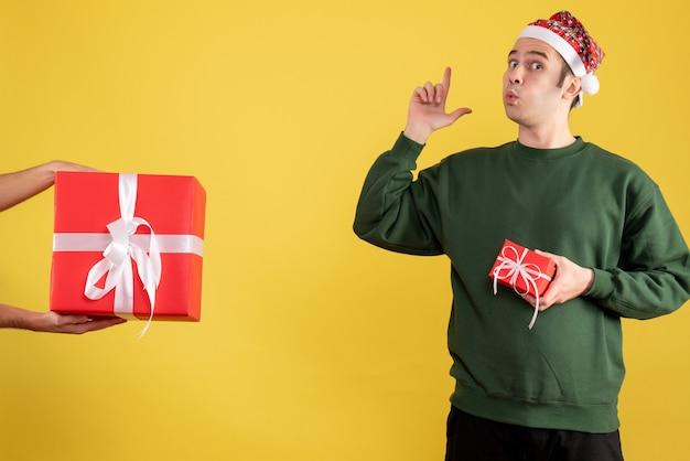 Vorderansicht junger mann, der fingerpistole macht, unterschreiben das geschenk in weiblicher hand auf gelb Kostenlose Fotos